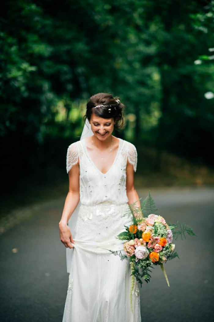 smiling woman in loosely fitting bridal gown inspired by 1920s fashion, looking down and holding her dress in one hand and a bouquet of colorful flowers in the other, trees and a road