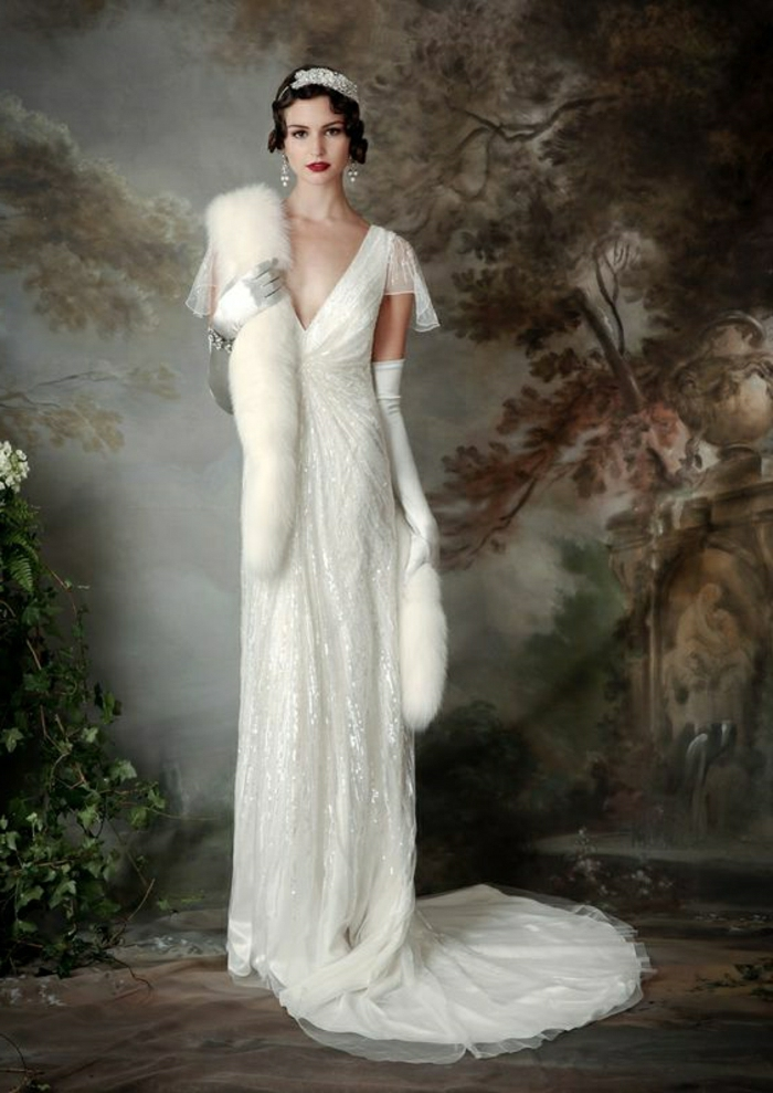 vintage inspired wedding dresses, dark-haired woman with a head ornament, standing in front of a large painting of nature, wearing long glittering dress, diamond earrings and a white fur scarf