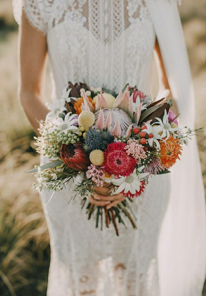 close-up of a bride in a lacy partly sheer dress, holding a bouquet with many different desert flowers in various colors