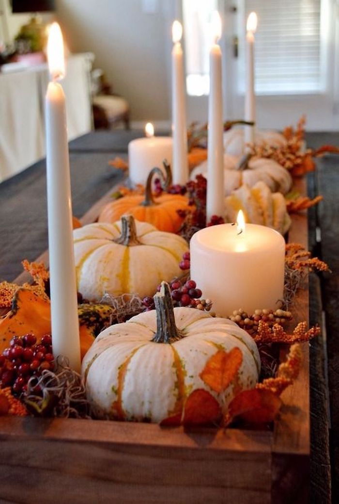 pumpkins in white and orange, placed on a wooden tray, with lit white candles, orange autumn leaves, decorative berries, on a dark table, room in the background