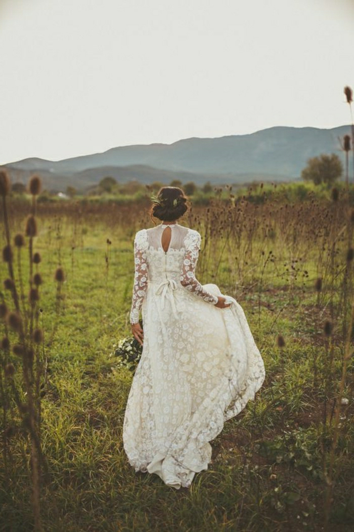 woman with brown hair in a fancy do, wearing a long vintage inspired dress with lace and sheer details, walking in a green field with thistles, holding her gown in one hand and a bouquet of white flowers in the other