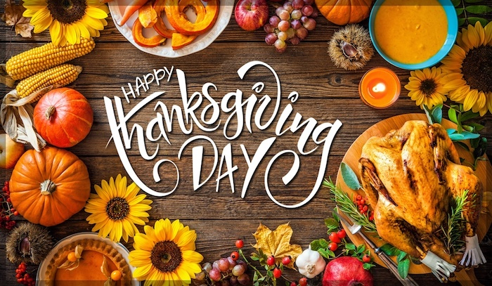 brown wooden table, happy thanksgiving day written in white fancy writing, plates of fruit and orange sauces, a cooked turkey, pumpkins, sunflowers, garlic, berries, corncobs, grapes, apples, chestnuts, pomegranate, orange and yellow autumn leaves