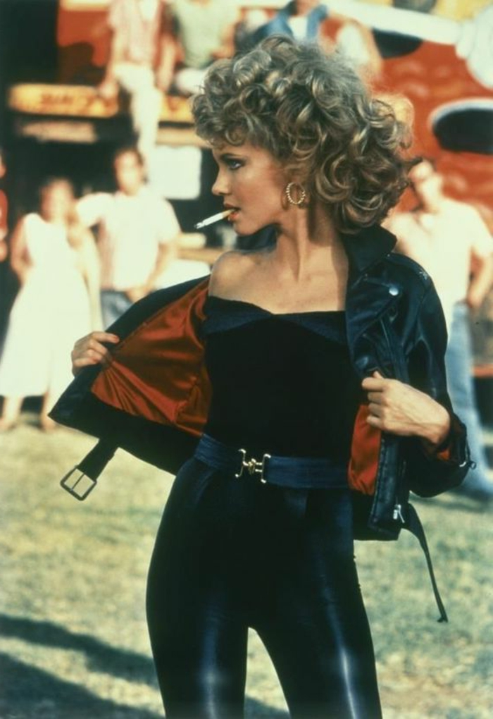 80s fashion trends, Grease, Olivia Newton-John, big curly blonde hair perm, black top and shiny black leggings, black leather jacket with red lining, wide belt and a cigarette
