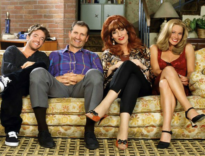 80s fashion, married with children sitcom family photo, 80s nostalgia fashion big red hair, cropped trousers and animal print top, plaid shirt and grey pants, smiling family sitting on yellow couch