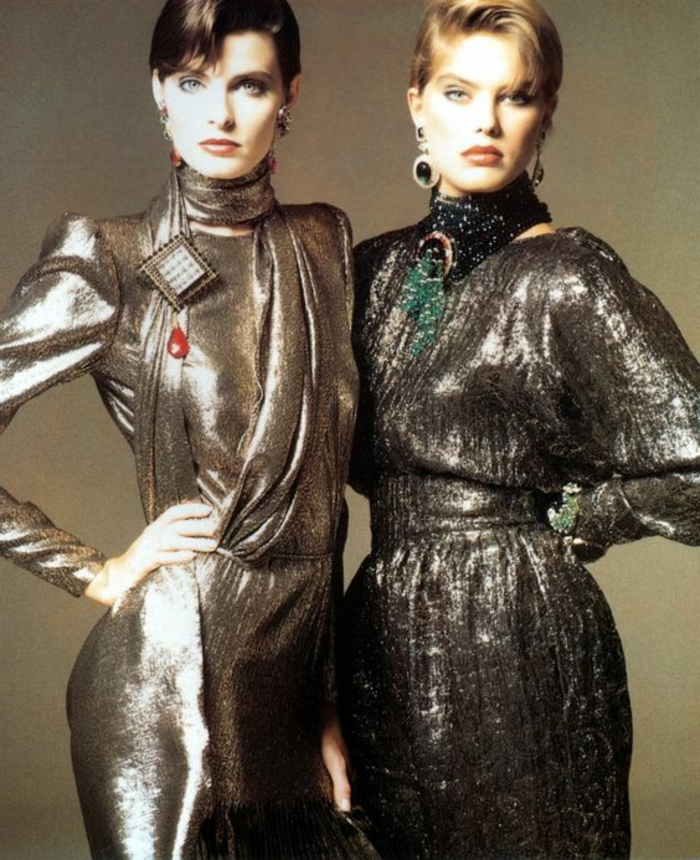 throwback outfits, two women with short brown and blonde hair standing next to each other, hands on hips and wearing 80s shiny silvery dresses with scarves and jewelry