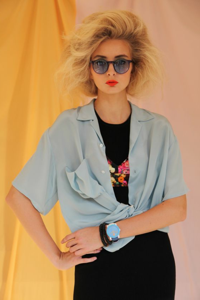 80s clothing, young woman with feathery died blonde hair, light blue short-sleeved tied shirt, black dress with flower embroidery, hands on hips and yellow curtains