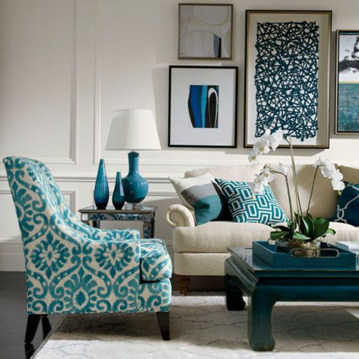 cream chair with blue pattern, black table and pale cream sofa with blue patterned cushions, white wall with plaster details, four framed images, blue lamp vases and trey white flower