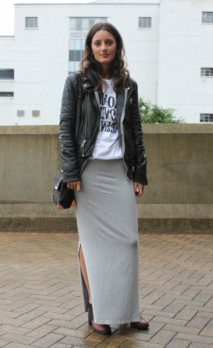 woman with curled brown hair and red lipstick, wearing big leather jacket, over white shirt with black print, grey jersey maxi skirt and ankle boots
