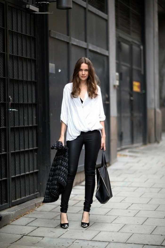 business casual attire for women, brunette woman wearing black skinny trousers, wide-fitting white shirt and black top, holding black and grey cardigan and black leather bag