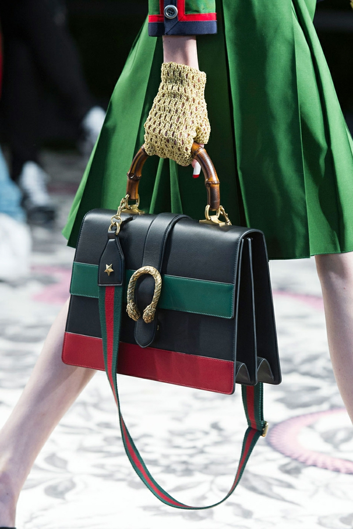 close up of black leather bag, green and red stripes, golden details and wooden handle, held by woman with yellow gloves, wearing green dress with red and blue details