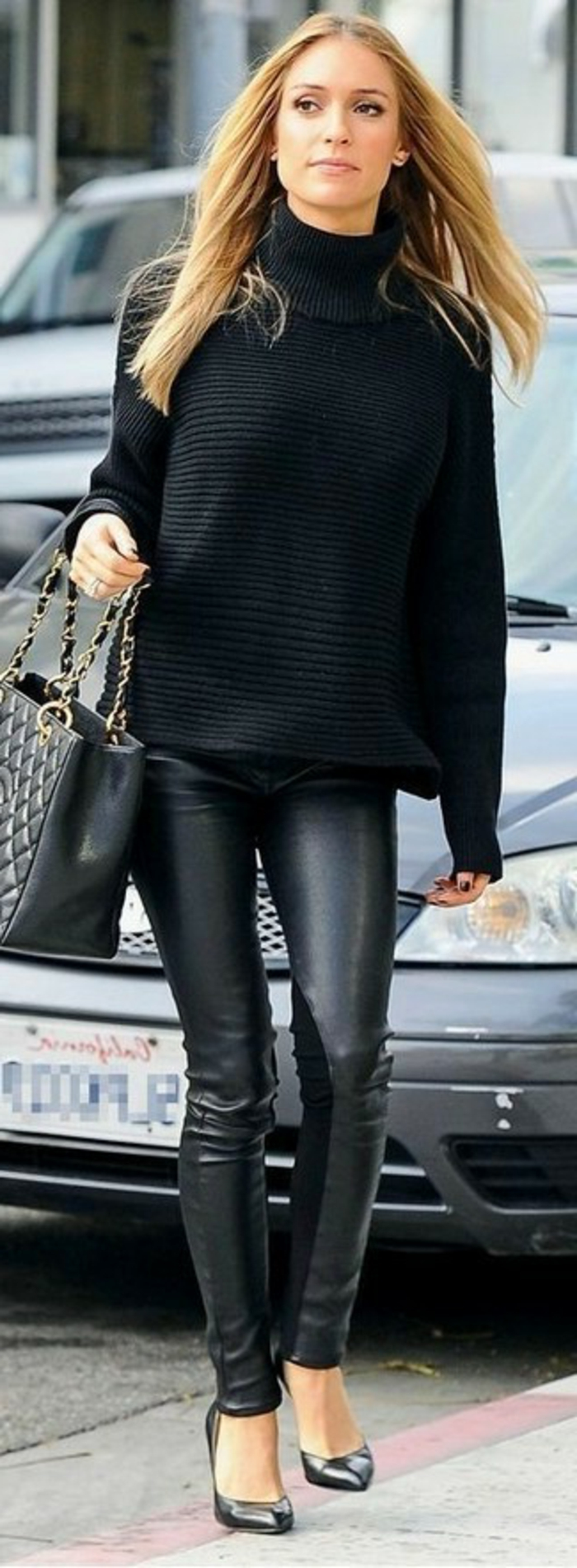 women's business attire, woman wearing black chunky turtleneck sweater, black leather skinny trousers and black high-heels, holding black leather bag