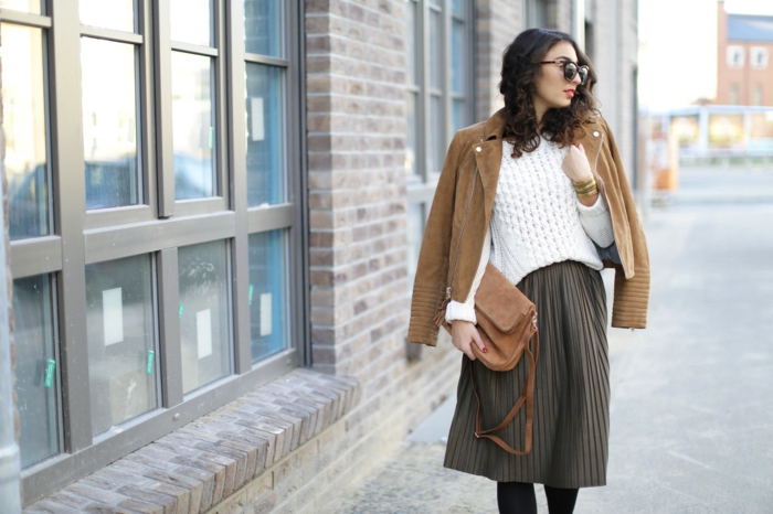 business casual attire for women, pleated knee-length brown skirt, white chunky knit sweater, camel brown leather biker jacket over shoulders, brown bag and sunglasses