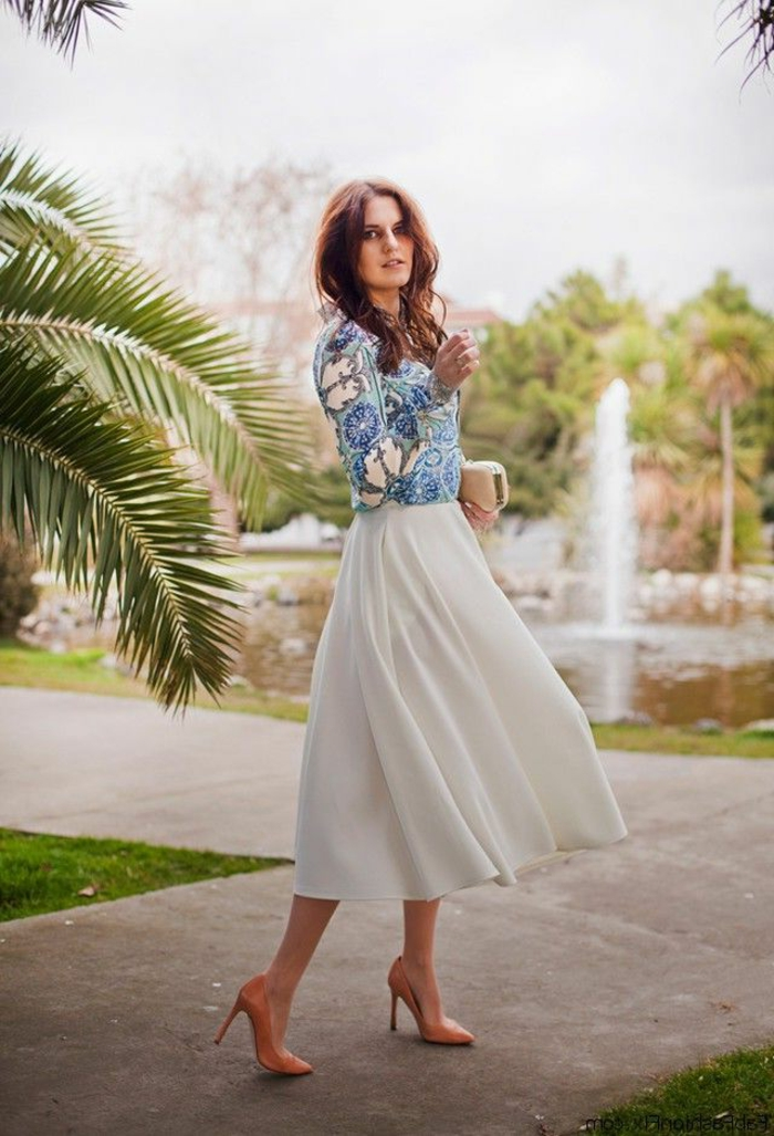 business casual attire for women, woman with wavy brown hair, wearing white floaty ankle-length skirt, nude pink stilettos and blue and white floral top