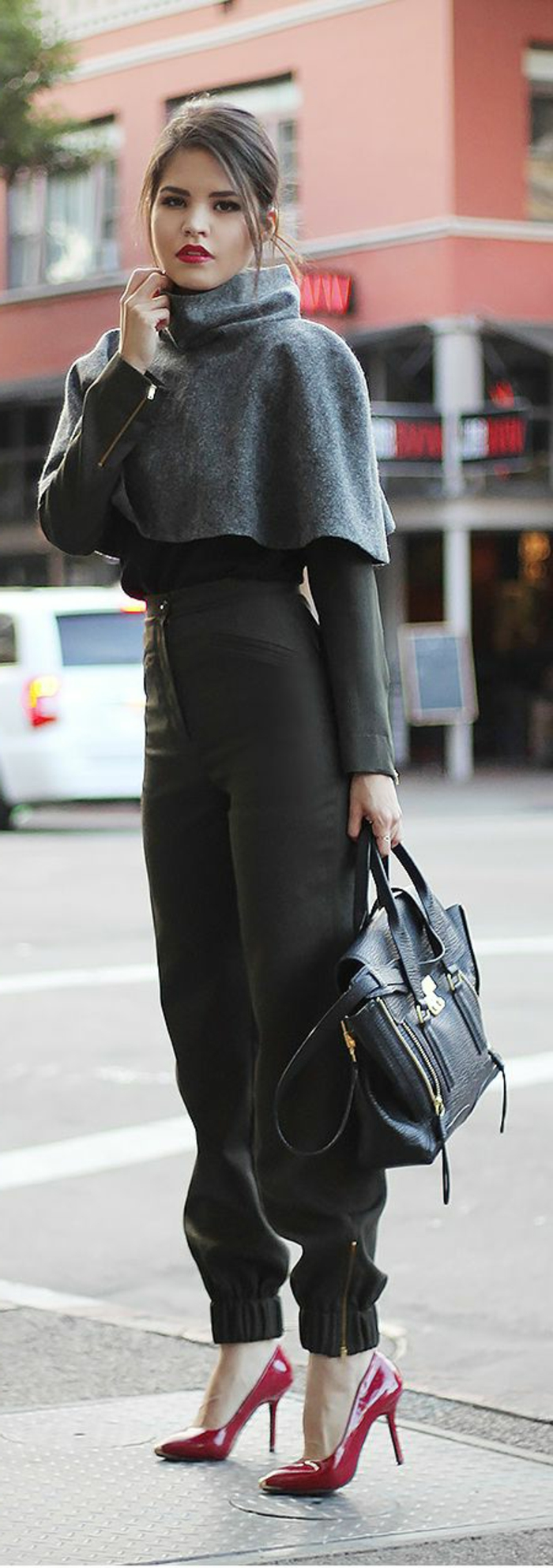 interview outfits for women, brunette woman with tied back hair and red lipstick, grey cropped turtleneck poncho over black top, black trousers and bag, dark pink high heels