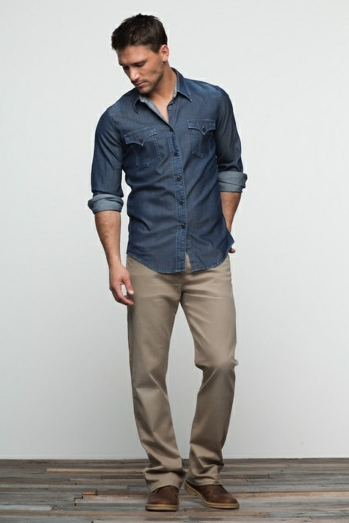 business casual outfits, man with short brown hair, looking down with hand in back pocket, pale khaki pants with denim shirt and brown shoes