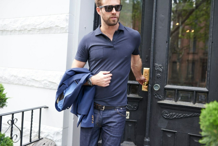 business professional attire, man with navy polo shirt, jeans with black belt and sunglasses, holding blue formal blazer