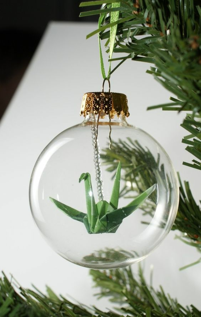 a small green paper origami crane, hanging on a small chain inside a clear glass bauble, golden cap attached to pine tree with green ribbon