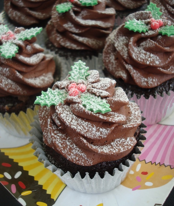chocolate cupcakes images, several chocolate cupcakes with chocolate frosting, decorated with fondant hollies and dusted with powdered sugar