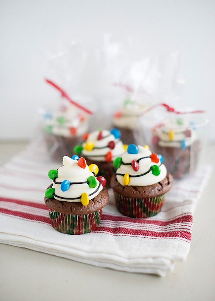 three chocolate cupcakes, with white frosting, decorated with chocolate drizzle and colorful candies made to look like christmas lights, three more wrapped cupcakes in background