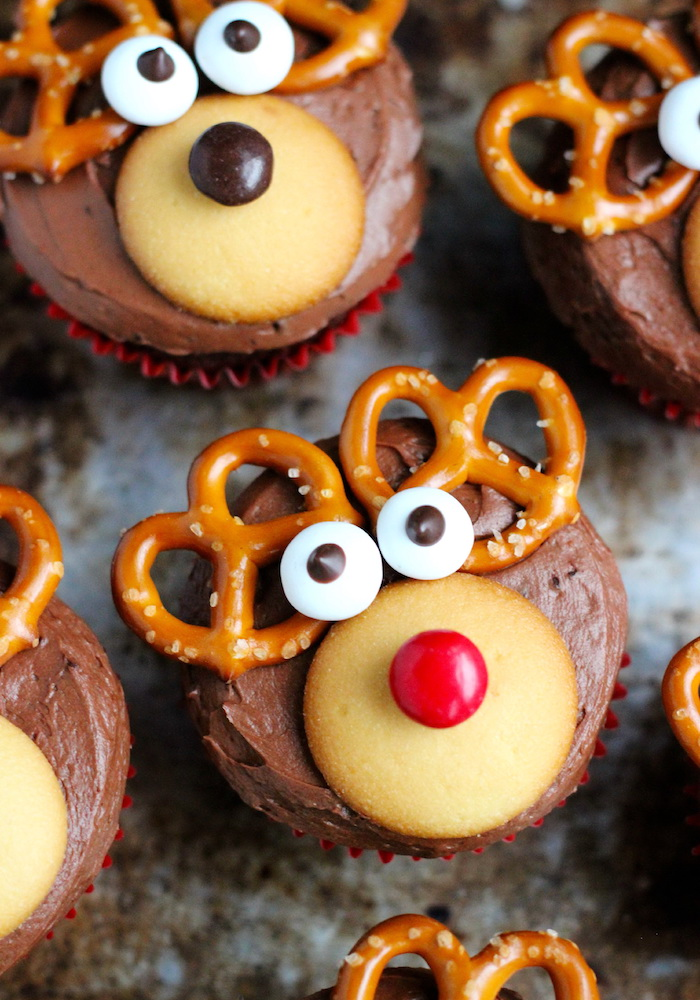 holiday cupcakes, close up of several cupcakes decorated with chocolate icing, yellow cookies candies and pretzels, made to look like reindeer