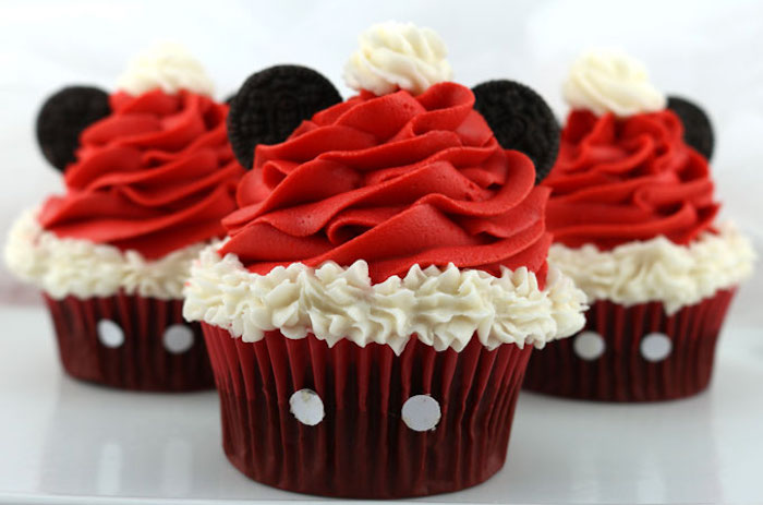 christmas flavors, three cupcakes with dark red wrappers, with red and white frosting and two oreo biscuits each, made to look like mickey mouse with a santa hat