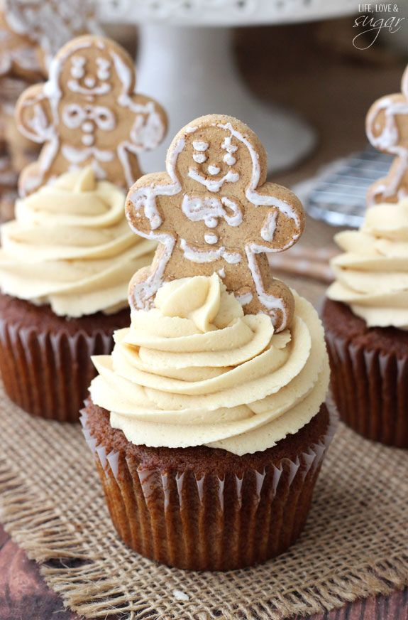 cupcake ideas, several dark cupcakes with light yellow creamy icing, decorated with gingerbread men cookies, on burlap tablecloth wooden table