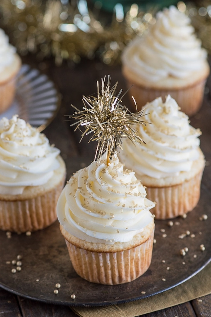 mini cupcake recipes, several light-colored cupcakes with white frosting, decorated with gold leaf pieces and golden-colored sparkler, on a dark plate with golden pearls