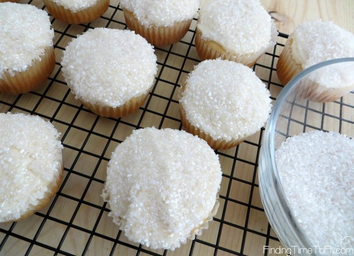 mini cupcake recipes, several cupcakes with white frosting, decorated with sparkly white sugar sprinkles, near a glass bowl with more sprinkles, on a black metal oven grate