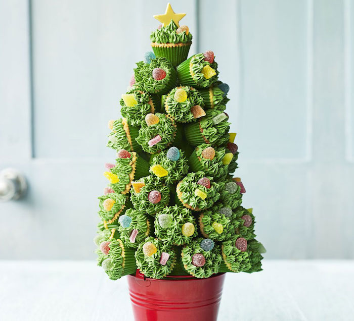 many cupcakes with green frosting, decorated with jelly candies, put in the shape of a christmas tree with red bucket on bottom and yellow star on top