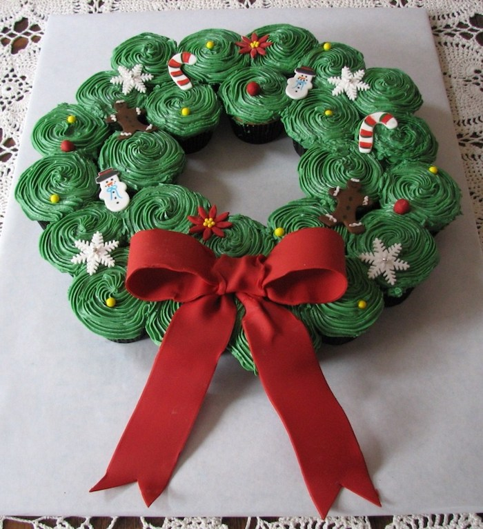 batch of cupcakes with green icing, decorated with festive fondant shapes, put in the form of a christmas wreath, decorated with big red fondant bow
