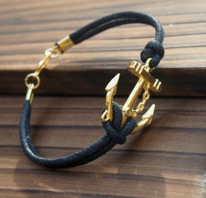 black woven leather bracelet with golden closure, featuring a golden anchor detail tied with knots, on wooden surface