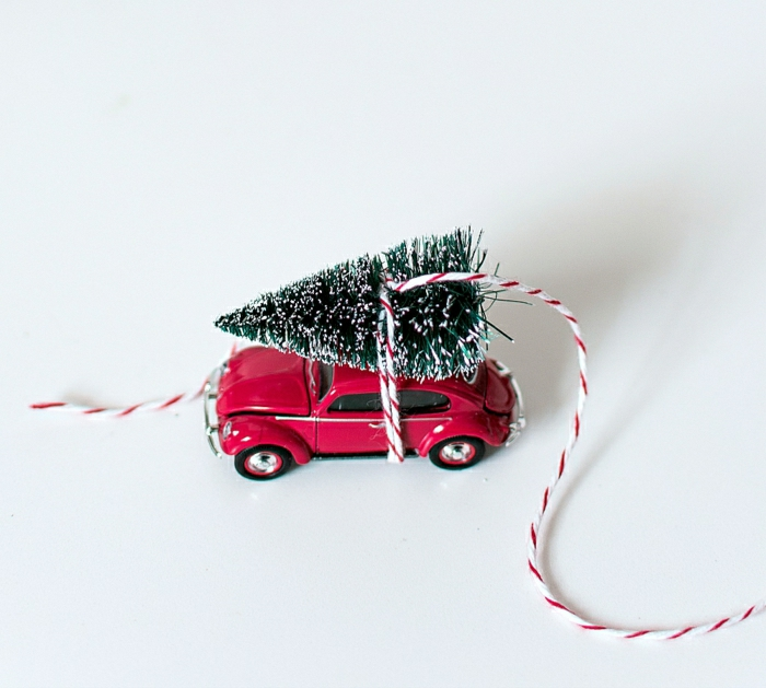 homemade christmas gift ideas, small xmas tree ornament tied to little red car toy with red and white string, white background