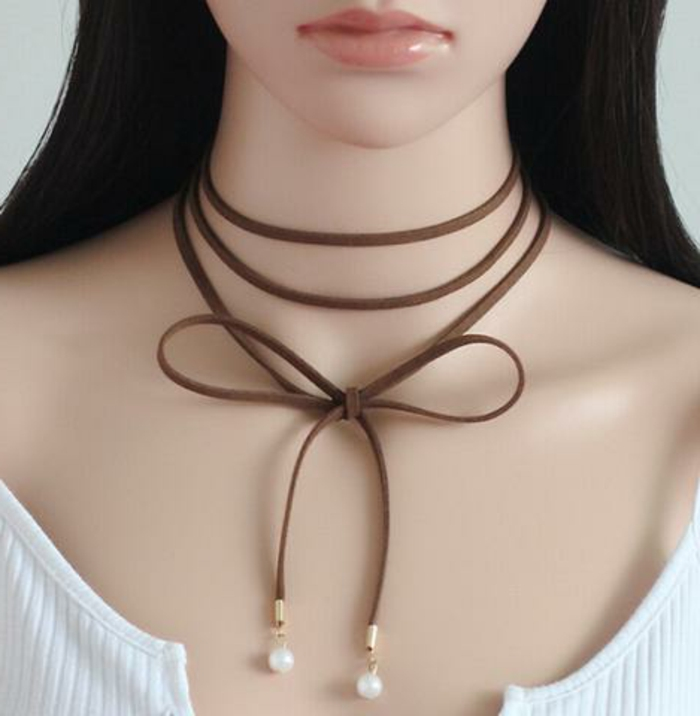 brown leather chocker, wrapped several times around a mannequin's neck and tied in bow, with pearl details