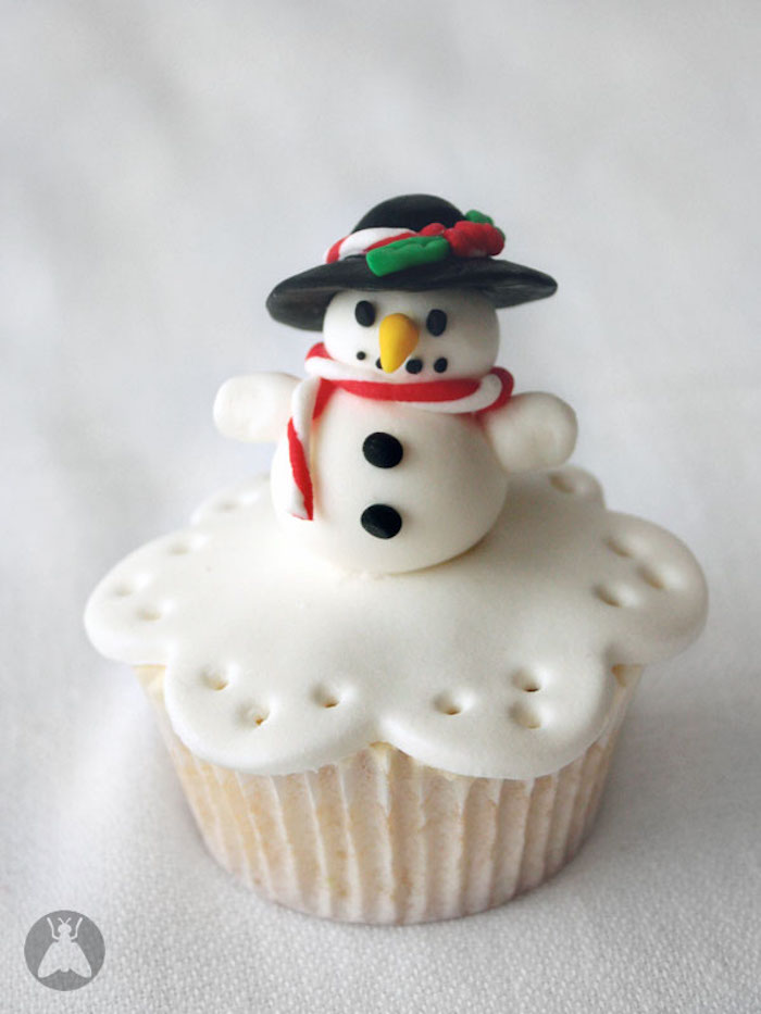 cupcake with white wrapper, and white fondant icing, decorated with snowman shape, wearing hat and scarf