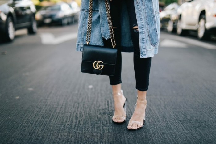 close up of woman's legs, wearing skinny distressed jeans and clear strappy high-heeled sandals, oversized denim coat with belt, small black bag with chain handle and metal detail