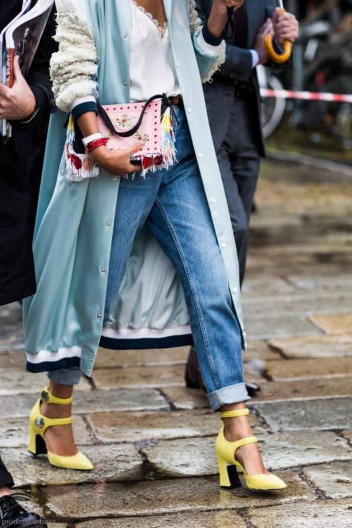 close up of woman's torso wearing rolled up jeans, yellow heels with wide straps, white lacy top and light blue over-sized bomber trench coat with fluffy sleeves, holding studded and tasseled clutch
