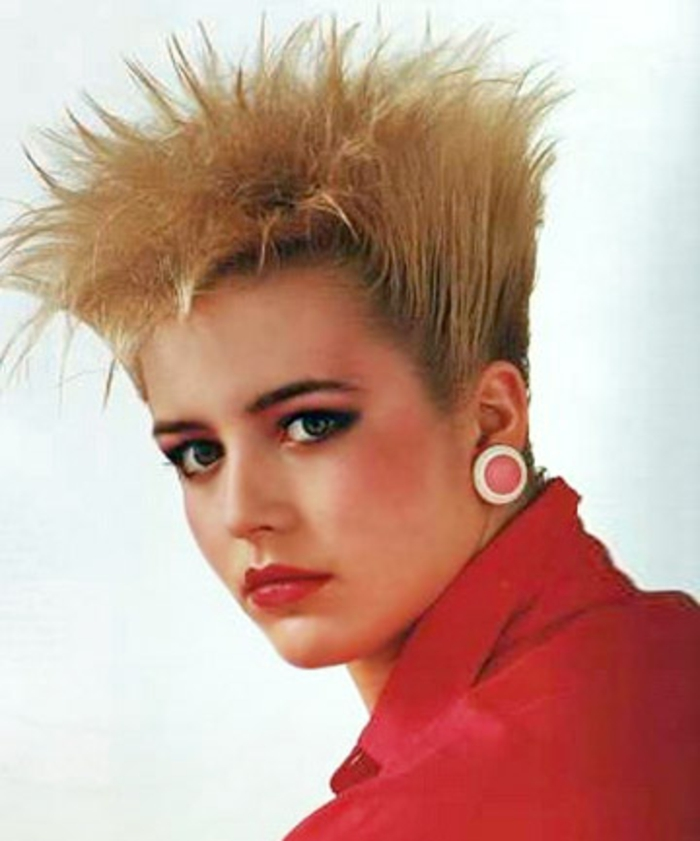 close up of blonde woman with 80s gelled up hi-top fade hair, red shirt and big round clip-on earring, red lipstick and heavy make up