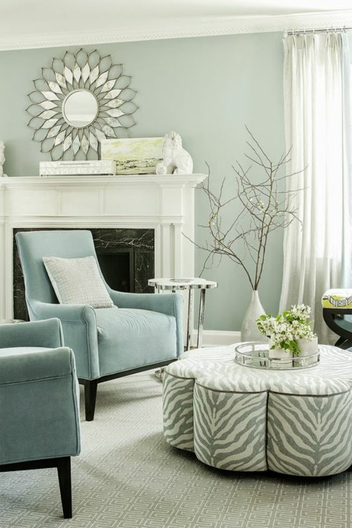 pale mint green room, two pale blue chairs, grey and white striped table, white fireplace and round ornate decorative mirror, white vase with dry branches