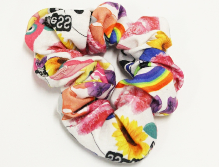 80s clothing, close up of colorful scrunchy, with sunflowers rainbows and writing, on white background