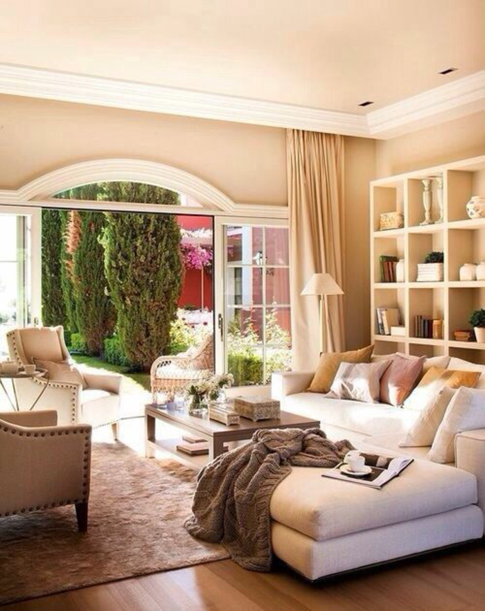 living room with pale orange walls and ceiling, white plaster details, cream sofa and chairs, light brown carpet and wooden floor, white shelves and cream curtains, grey blanket and glass door opened to garden