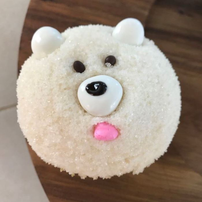 mini cupcake recipes, cupcake with white sparkly sugary icing, decorated with fondant and chocolate to look like polar bear, on a dark wooden table