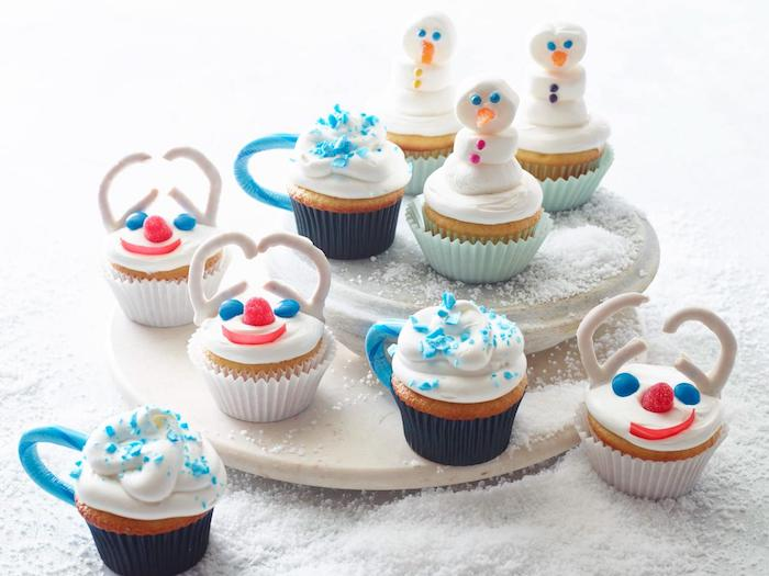 batch of cupcakes with white frosting, in white dark blue and light blue wrappers, decorated with candies to look like snowmen and cups
