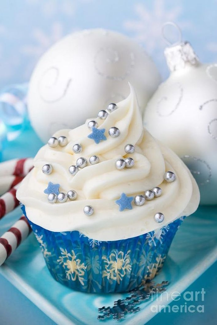 cupcake in blue wrapper, with white snowflake pattern, white icing decorated with small blue stars and silver pearls