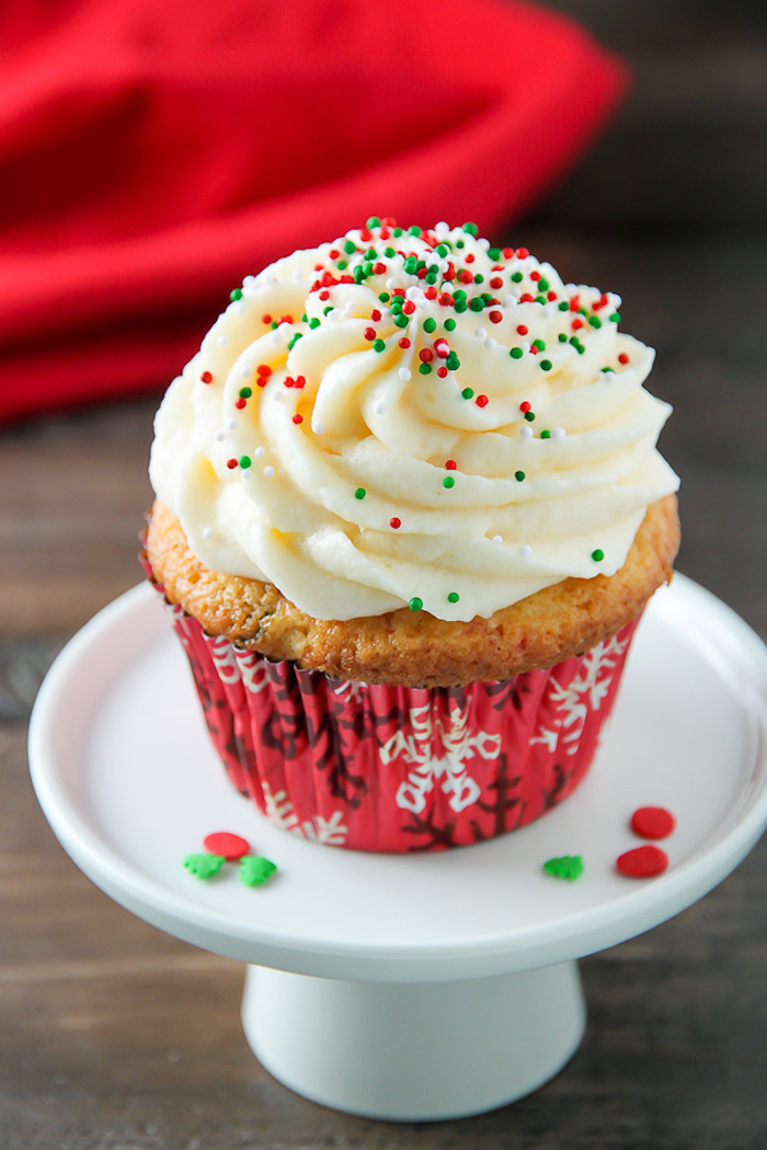 christmas baking ideas, yellow cupcake in red wrapper, with pale yellow creamy icing, decorated with red and green sprinkles