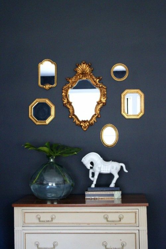 six differently sized and shaped ornate mirrors with golden frames, white chest of drawers with brown top, blue glass vase with green plant, books and a white horse statuette, dark blue background