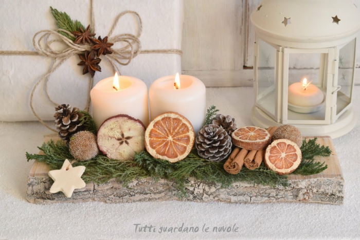 christmas crafts for adults, a chunky wooden board with two ccandles, decorated with pine cones cinnamon sticks a star-shaped cookie, with wooden circles painted like fruit slices, lantern and wrapped gift in background