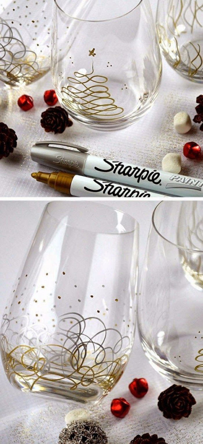 several plain water glasses, decorated with gold and silver permanent markers, abstract Christmas tree drawing and different shapes, little pine cones red and white beads