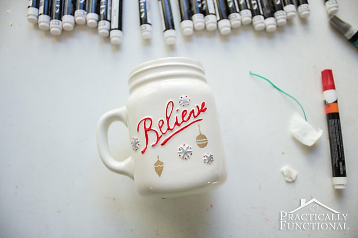 diy christmas crafts, red marker near white hand-painted mug, believe written in red and hand-painted details, markers in upper part of background, on white surface