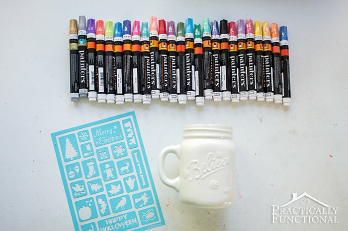 diy christmas crafts, many markers in different colors, near a white empty mug with handle, a blue holiday-themed stencil, on white surface