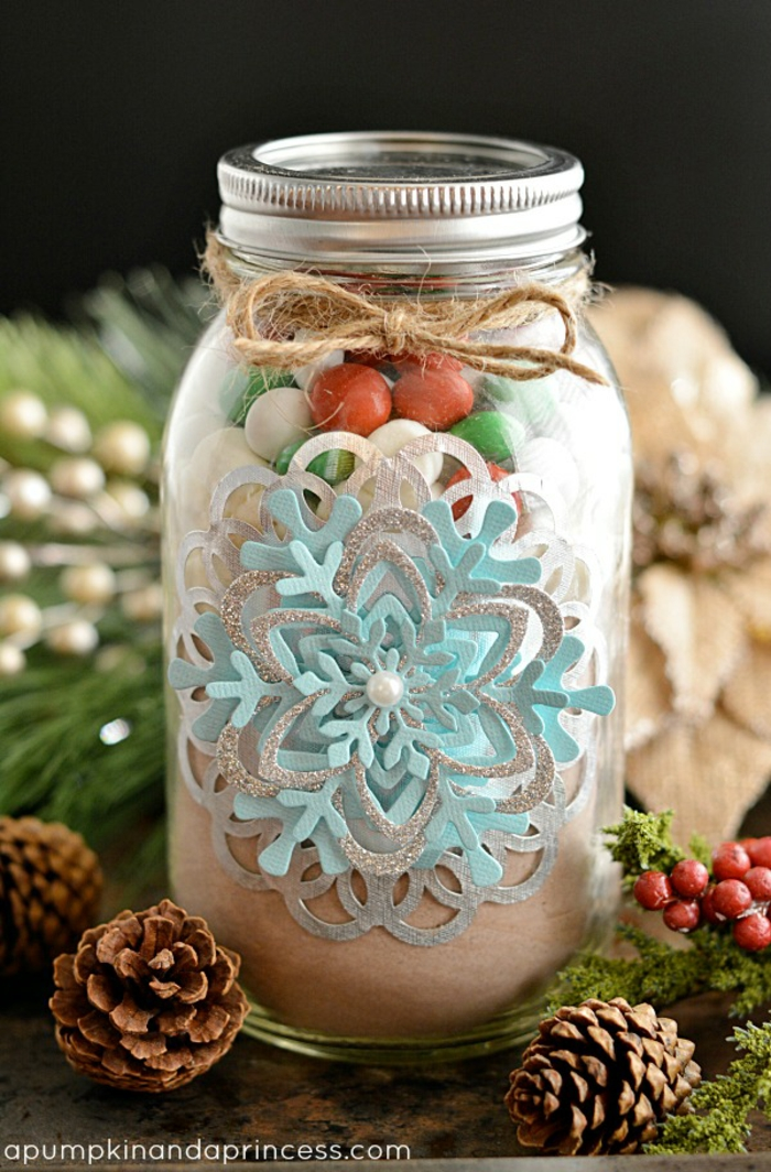 christmas crafts for adults, a big clear mason jar filled with sweets, with beautiful snowflake-shaped paper decoration and a pearl, tied with plain string, near pine cones and berries